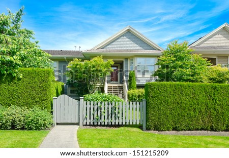Nice looking house behind the wooden and nicely trimmed green fence at the empty street in the suburbs of Vancouver, Canada. - stock photo