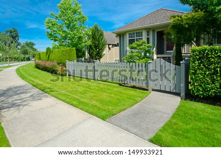 Nice looking house behind the wooden fence and pedestrian sidewalk at the empty street in the suburbs of Vancouver, Canada. Neighborhood scenery, landscape design. - stock photo