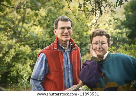 Nice looking late middle age to senior retired couple relaxing outdoors - stock photo
