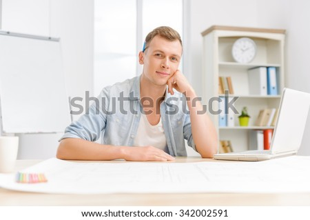 Nice-looking man. Young attractive office employee is sitting at his desk and smiling gently.