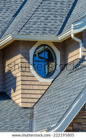Nice looking window at the roof, upper level of the house. - stock photo
