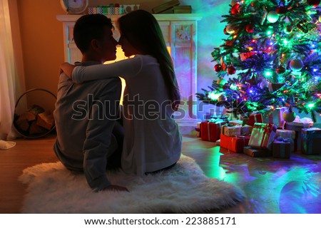 Nice love couple sitting on carpet in front of fireplace. Woman and man celebrating Christmas - stock photo