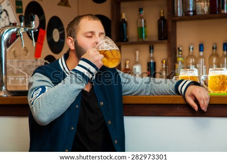 Nice man at bar drink glass of light beer. horizontal photo - stock photo