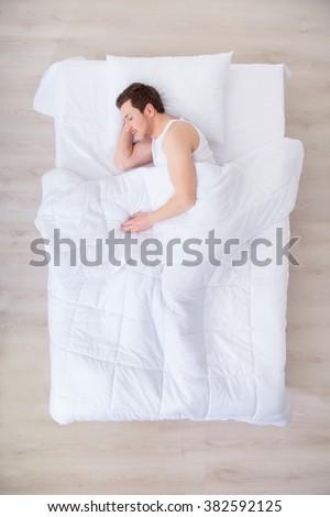 Nice man sleeping in  bed  - stock photo
