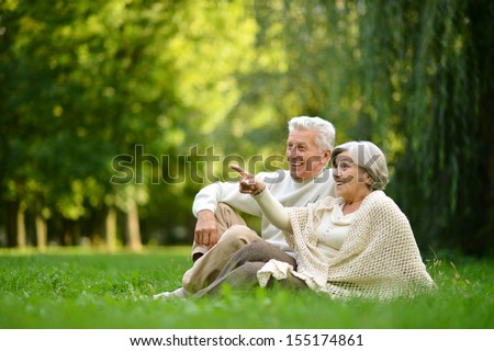 Nice mature couple sitting on green grass in summer park. Woman pointing with finger - stock photo