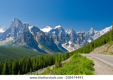Nice mountain road over fantastic rocky mountains, Banff National Park, Alberta, Canada. - stock photo