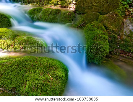 nice mountain stream with green stones - stock photo