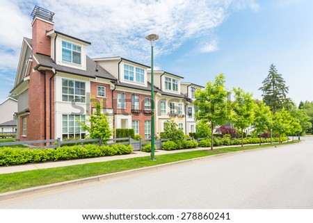Nice neighborhood on a sunny day. Townhouses in the suburbs of the North America. Canada. - stock photo