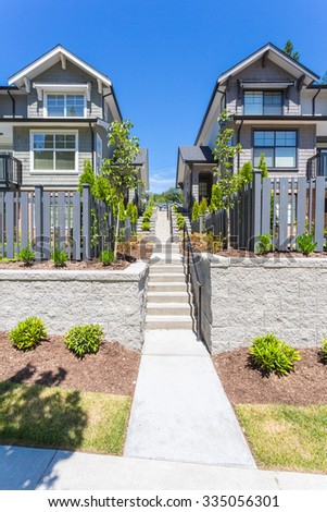 Nice neighbourhood on a sunny day. Townhouses in the suburbs of the North America. Canada. - stock photo