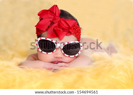 Nice newborn baby girl posing with sunglasses on  yellow fur and white background wearing a red ribbon. - stock photo