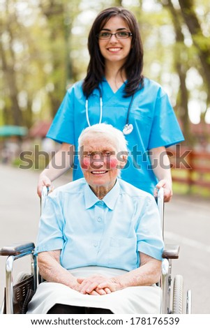 Nice nurse walking with elderly lady in wheelchair. - stock photo