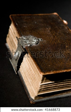 Nice old bible with an old lock on a black background.
