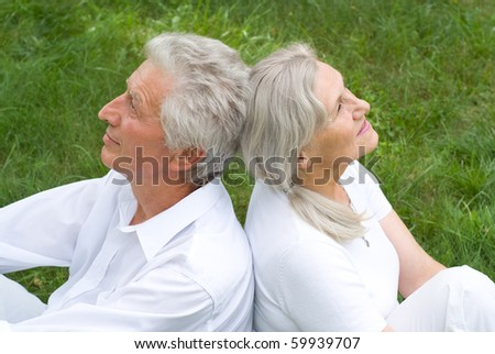 nice old couple in a summer park - stock photo