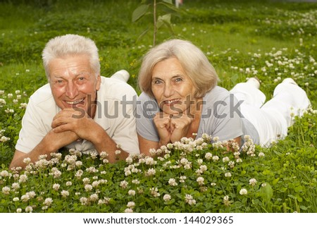 Nice old couple in the middle of the lawn with white flowers