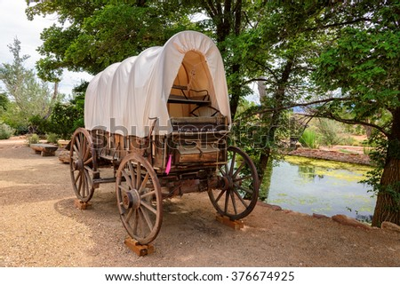 Nice old covered wagon in Arizona and lake in background - stock photo