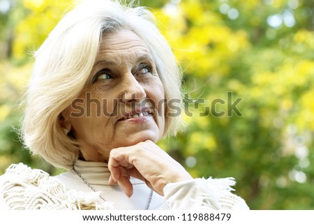 nice old woman standing in a autumn