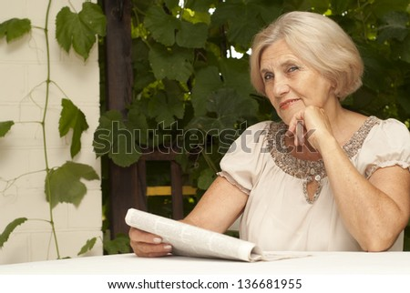 Nice older woman sitting at a table at home on the veranda