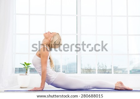 Nice photo of beautiful woman practicing yoga. Woman meditating with her eyes closed while doing cobra pose. White interior with large window - stock photo