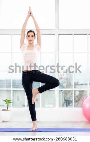 Nice photo of young woman practicing yoga. Woman meditating while doing tree pose. White interior with large window
