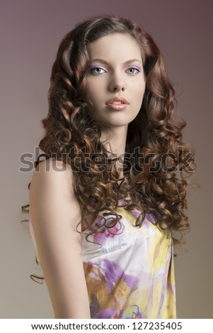 nice portrait of a curly haired young woman with floral dress looking in camera - stock photo