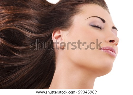 nice portrait of a cute brunette with her long hair in the wind enjoing the breeze with closed eyes