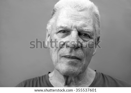 Nice portrait of a senior thoughtful man with a light smile, in black and white - stock photo