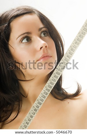 nice portrait of a young brunette looking at the tape measure with surprise - stock photo