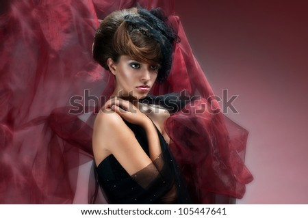 nice portrait of an attractive young girl with well done hair and delicate makeup black evening dress and covered with red material - stock photo