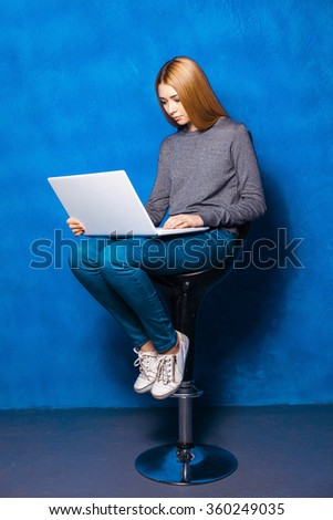 Nice portrait of beautiful girl on blue background. Young woman sitting on high chair and using laptop - stock photo
