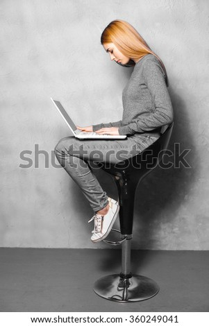 Nice portrait of beautiful girl on grey background. Young woman sitting on high chair and using laptop - stock photo