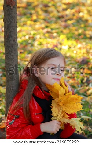 Nice portrait of cheerful cute young girl in the park/Image of pretty and beautiful face of lovely european little girl in autumn season - stock photo