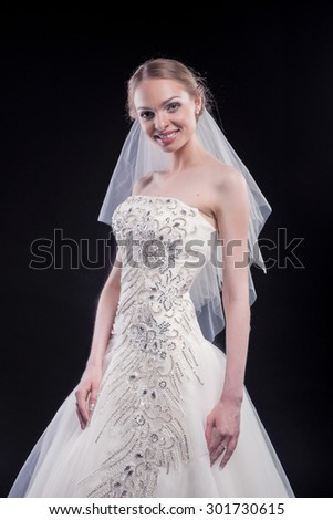 Nice Portrait of Sensual Caucasian Female Bride in Beautiful Nicely Tailored Wedding Dress Posing Against Black. Vertical Image Orientation