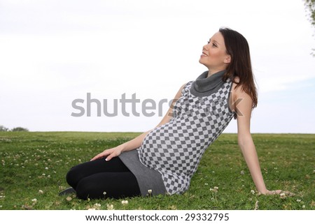 Nice pregnant woman sitting on a lawn