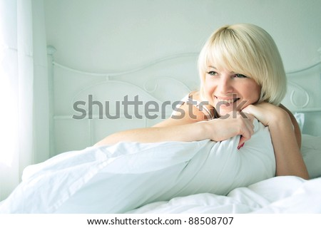 Nice pretty girl smiling in bed in the morning