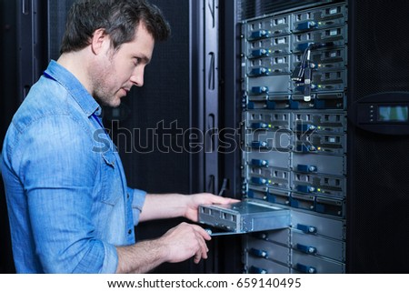Nice professional technician installing the blade server