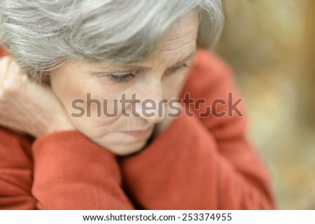 Nice sad old woman on the autumn background - stock photo