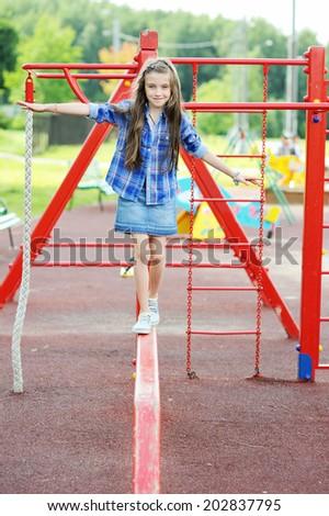 Nice school age kid girl has fun on the colorful playground  - stock photo