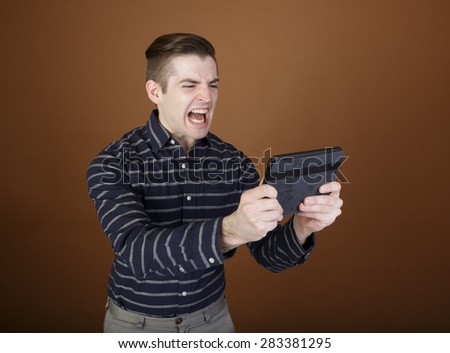 Nice shot of a young man screaming at his tablet in a casual outfit on a brown background with room for copy - stock photo