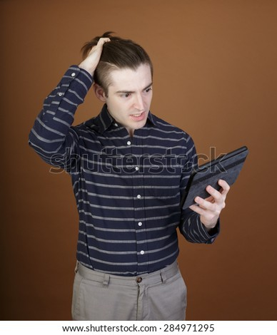Nice shot of a young man using a tablet reacting to the content in a casual outfit on a brown background with room for copy - stock photo