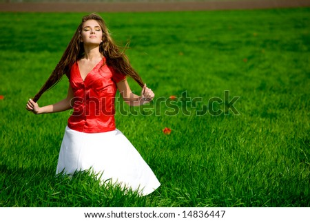 Nice slim girl relaxing in grass. It's windy and sunny. - stock photo