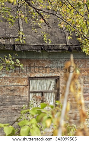 Nice small window of old abandoned wooden house in garden - stock photo