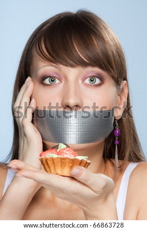 Nice smart girl do her best no to eat cake with worry in her eyes and sticky tape on her mouth - stock photo