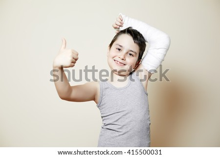 nice smiling boy with hand in cast with hand on head - stock photo