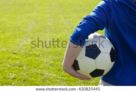 Nice smiling happy 8 years old boy stand with volleyball ball in the park field outside on sunny summer day - stock photo
