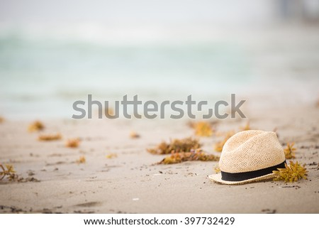 Nice straw hat laying on the sand. Beautiful ocean beach background. Outdoors. Vacation time. End of summer vacations. Dreaming of holidays by the sea. Traveling. - stock photo