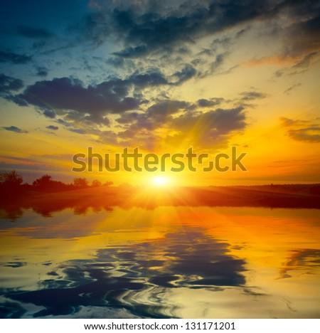 Nice sunset over lake - stock photo