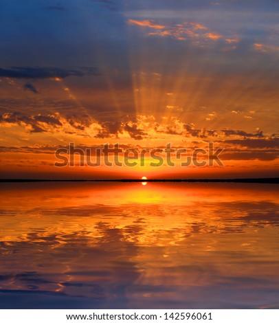 Nice sunset over lake surface - stock photo