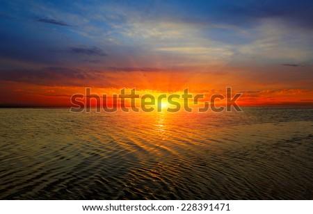 Nice sunset over sea surface - stock photo