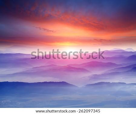 Nice sunset scene over misty mountains - stock photo