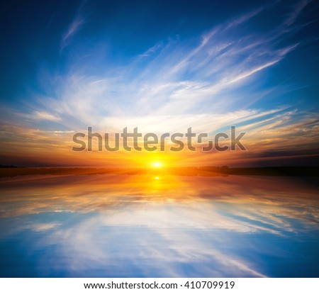 Nice sunset sky over lake water surface - stock photo